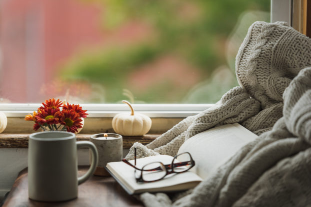 cozy nook near window with book, reading glasses, coffee mug and fall decor