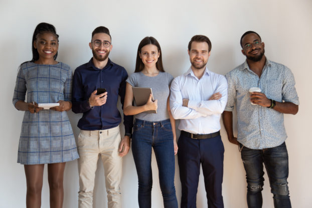 group of diverse coworkers standing in a line and smiling