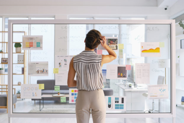 woman writing on clear board in office