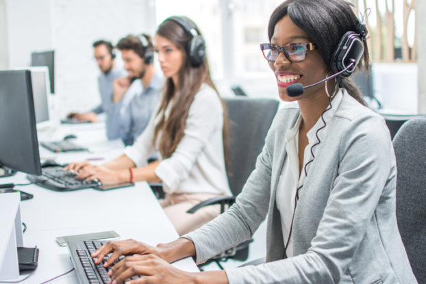 employees working on computers with headsets