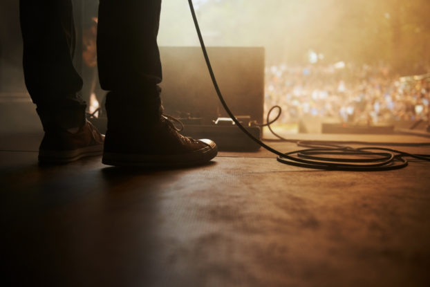 person's feet on stage at a live music venue