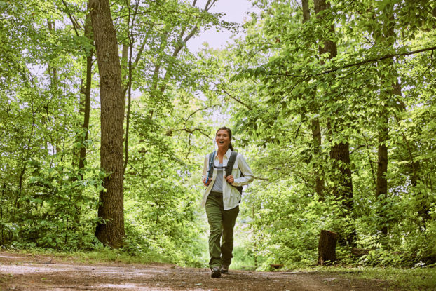 A woman wearing a backpack walks on a trail through a forest.