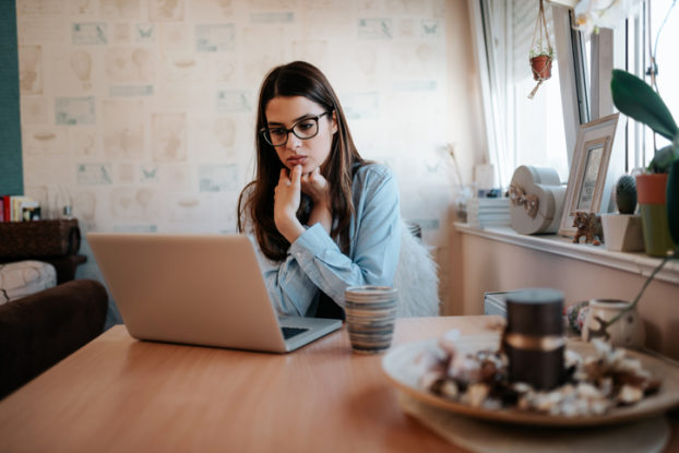 woman thinking while looking at laptop