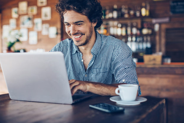 man smiling at laptop in a coffee shop