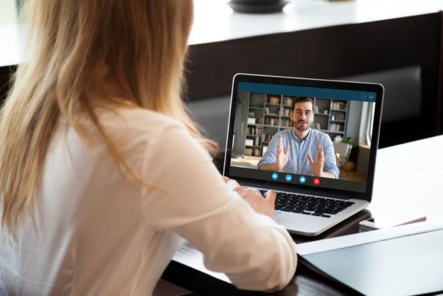 Two colleagues conduct a performance review on video chat.