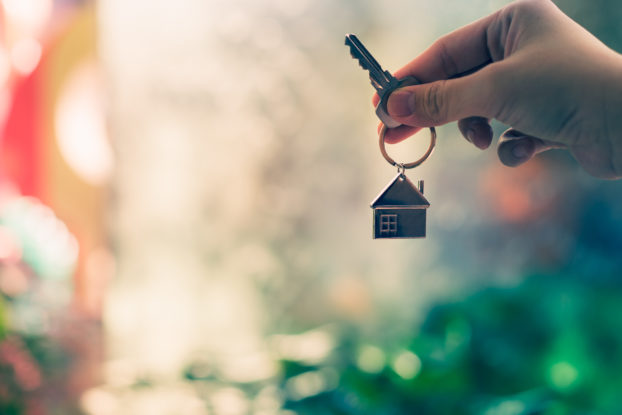 person holding key with house keychain