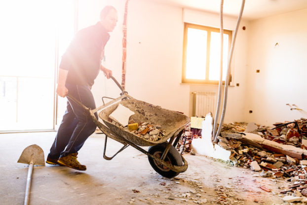 man with wheelbarrow in damaged building