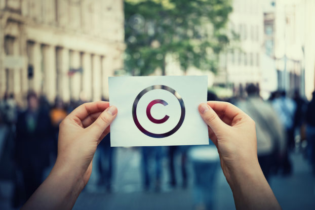 person holding copyright symbol