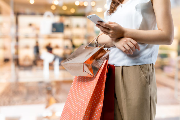 woman holding shopping bags and phone