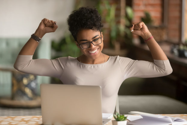 Woman looking at her laptop pumps her fists in the air and smiles