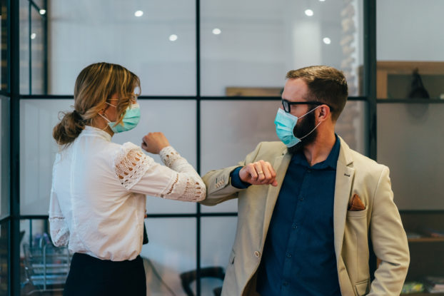 two coworkers with masks bumping elbows