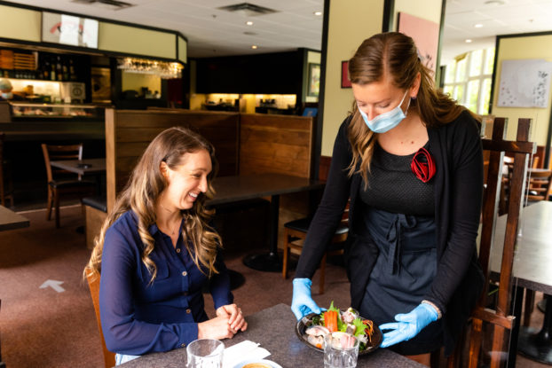 woman serving customer with mask in restaurant