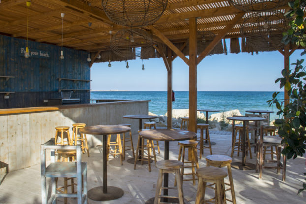Outdoor beachfront bar with stools, empty and ready for patrons to arrive.