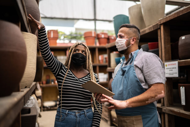 A Black woman gestures to a shelf of planters as she talks with an apron-wearing man with vitiligo. Both people are wearing face masks.