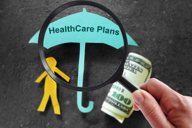 paper cutout of person and umbrella about cost of health care