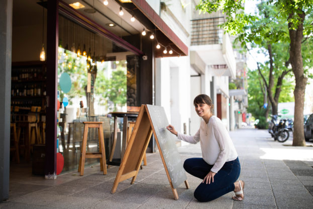 woman outside shop writing on chalkboard