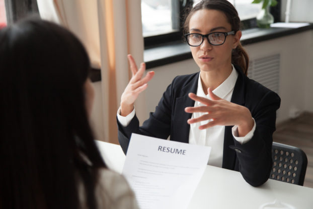 A woman in glasses talks to another woman, who faces away from the camera and holds the first woman's resume.