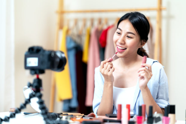 female influencer recording a video putting on makeup