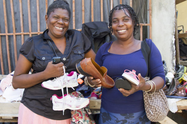 two women holding shoes for soles4souls