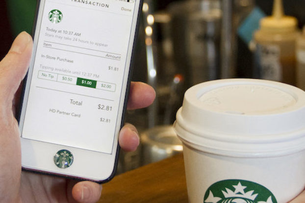 person holding starbucks cup and phone with starbucks app