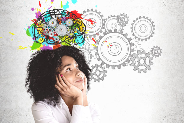 woman smiling brainstorming with wheels turning in the background