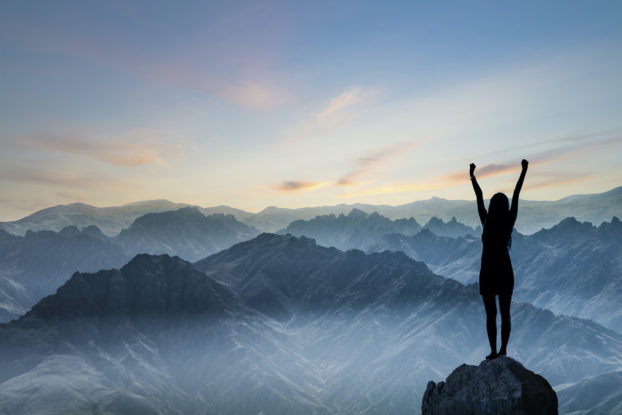woman standing on top of a mountain with her arms up