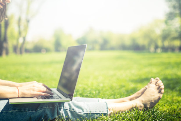 woman sitting in grass on laptop