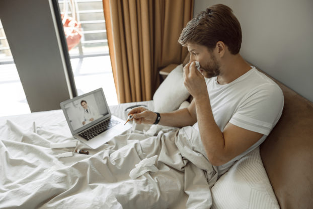 man sick in bed on laptop with telehealth doctor