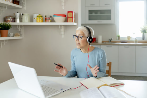 woman working from home talking on headset at dining room table