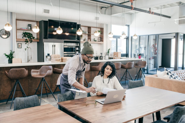 two people inside their business working on a laptop