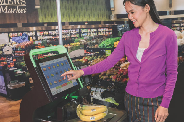 woman using self-checkout in supermarket