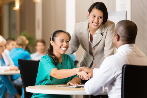 Three people meeting at a job fair where one is interviewing the other at a table.