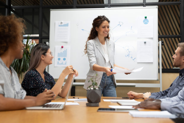 woman presenting to coworkers in a meeting in front of a whiteboard
