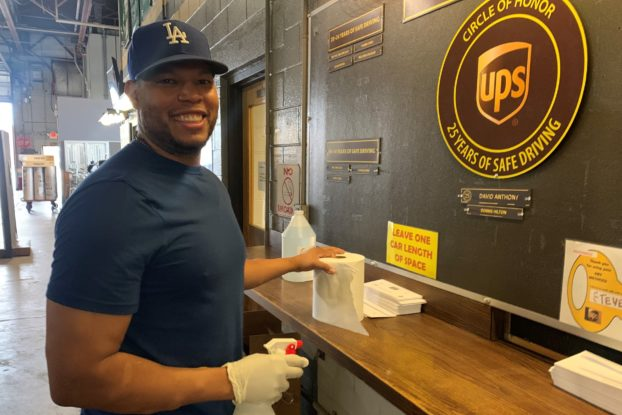 UPS employee cleaning surface at work