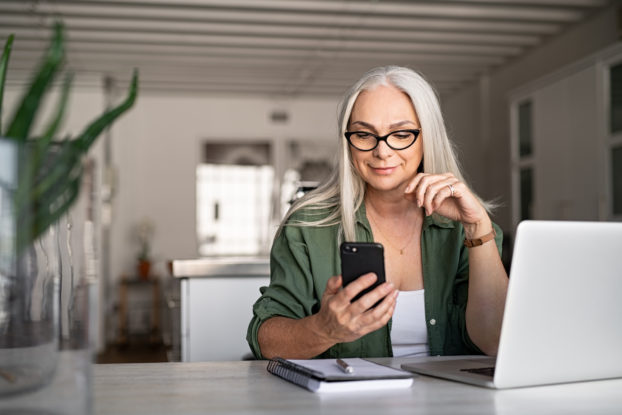 woman on phone and laptop working from home