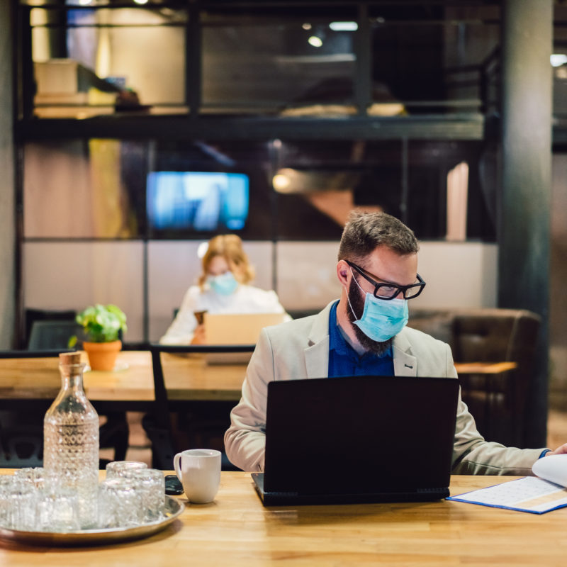 two employees working in office with masks on