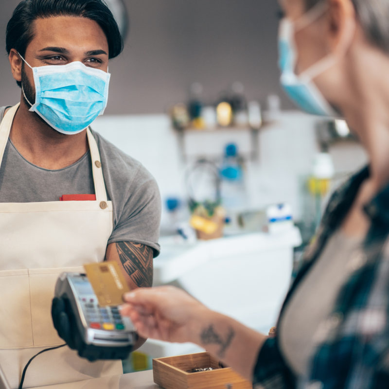 customer paying employee with credit card while wearing masks