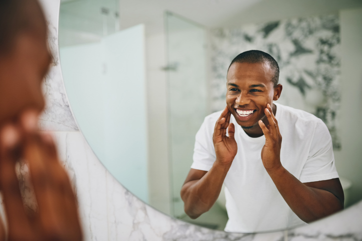 man looking in mirror touching his face